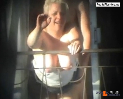 Amateur MILF is waving to voyeur during sex on balcony VIDEO