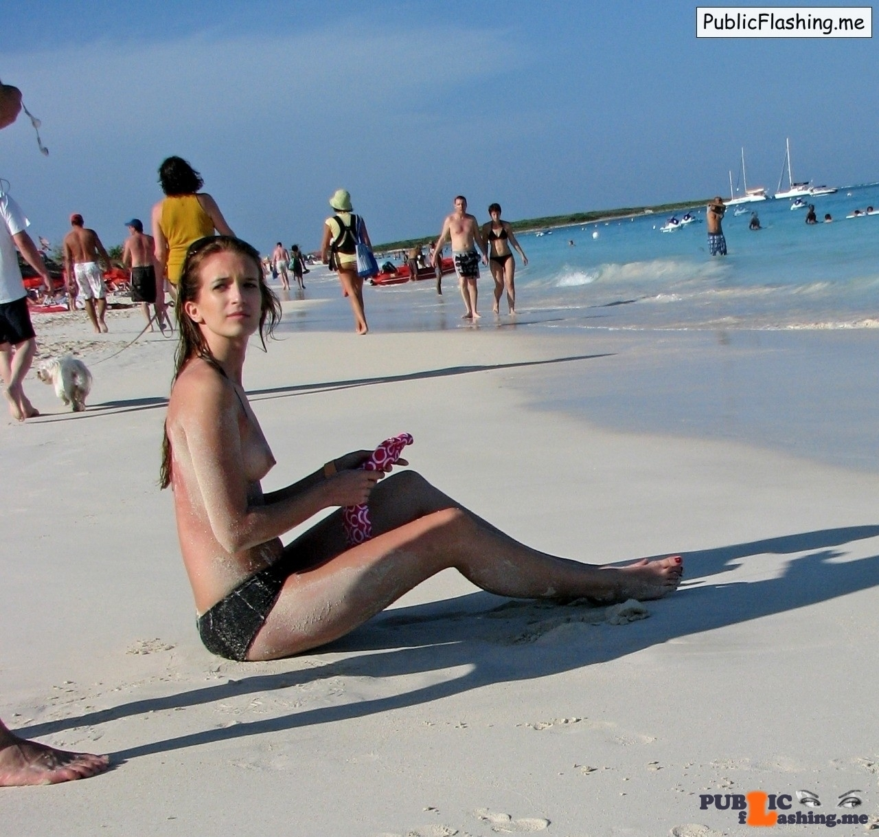 Teen brunette is sitting in the sand topless
