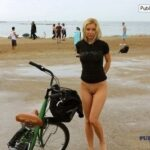Bottomless blonde and a bicycle on the beach