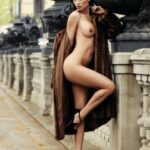 Fully nude dark haired babe posing in fur coat and high heels in public