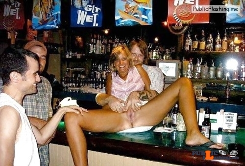 Mature blonde surrounded with men is spreading legs on bar